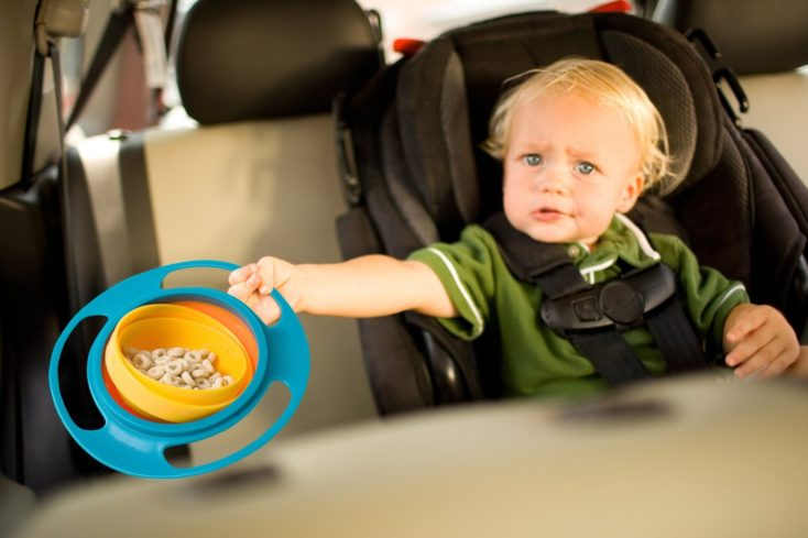 a toddler with a gyro bowl in a car